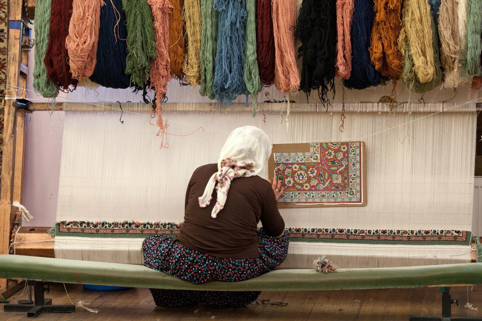 Turecká žena plete hedvábný koberec | wjarek/123RF.com